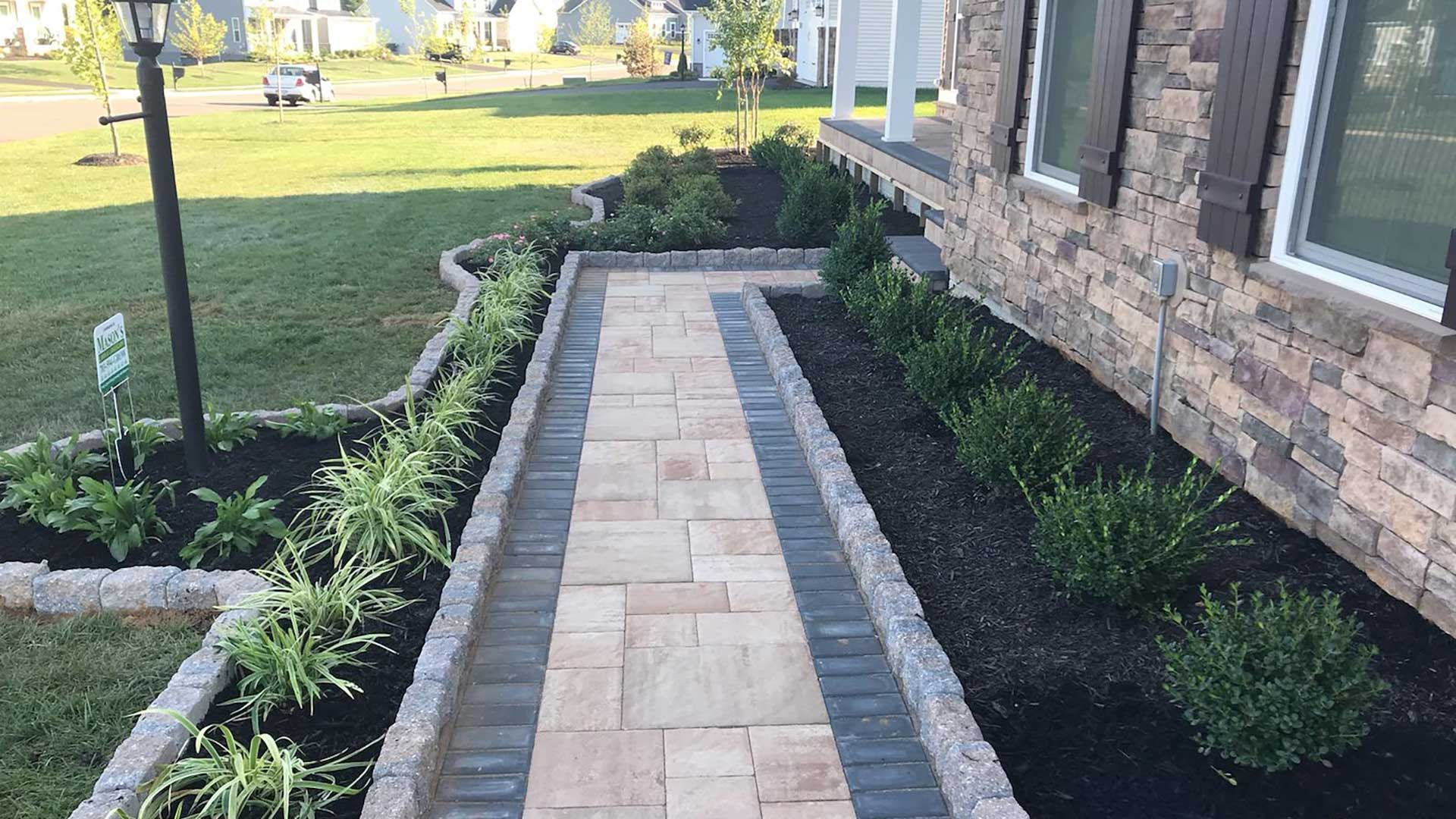 Custom walkway and landscape bed installation with plantings in Warrenton, VA.