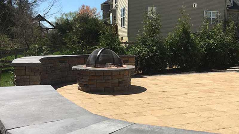 Custom fire pit and patio construction with seating wall near Gainesville, VA.